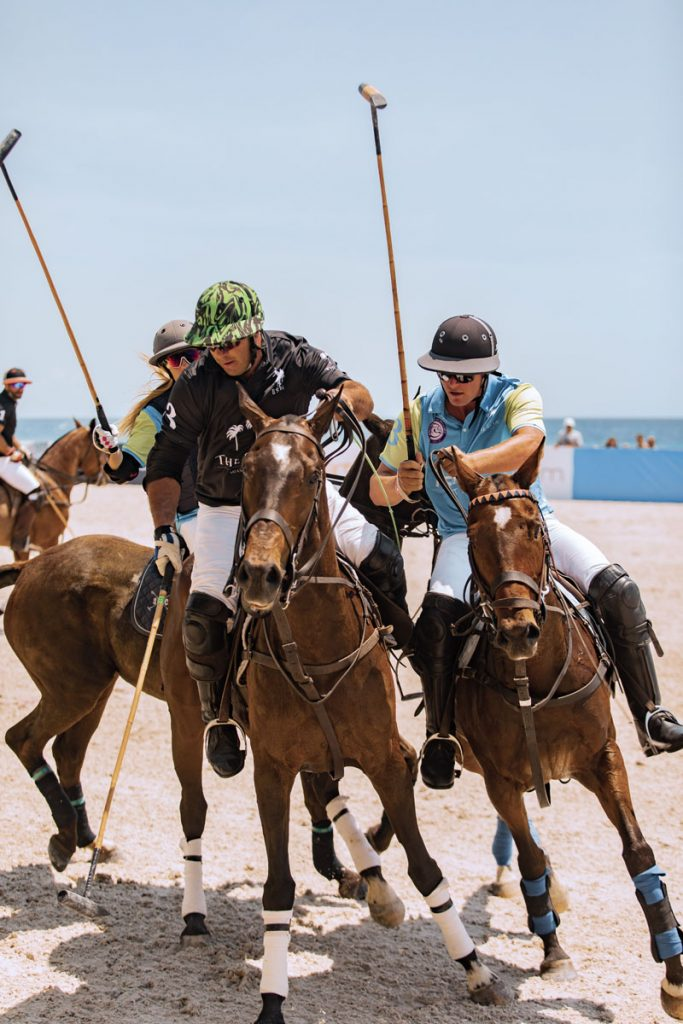 Pedro Soria and Jason Crowder close in on the ball in a 2019 World Polo League Beach Polo match. Photo by Alchemy