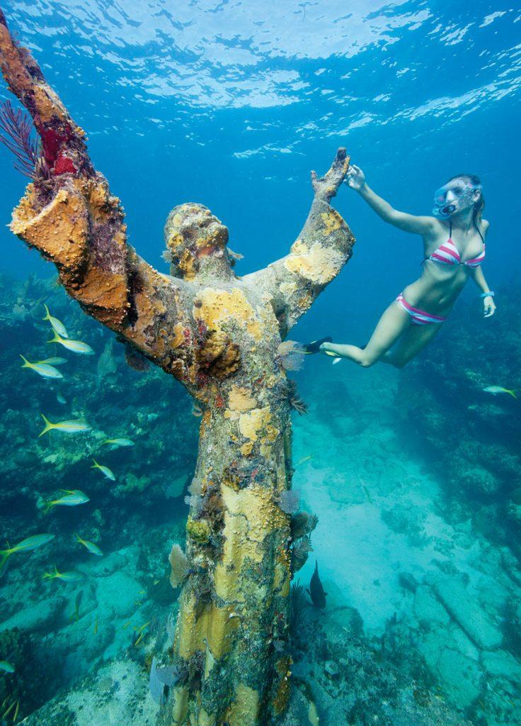 Snorkeler Katherine Wieland examines the Christ of the Abyss statue in the Florida Keys National Marine Sanctuary off Key Largo. Photo by Stephen Frink/Florida Keys News Bureau